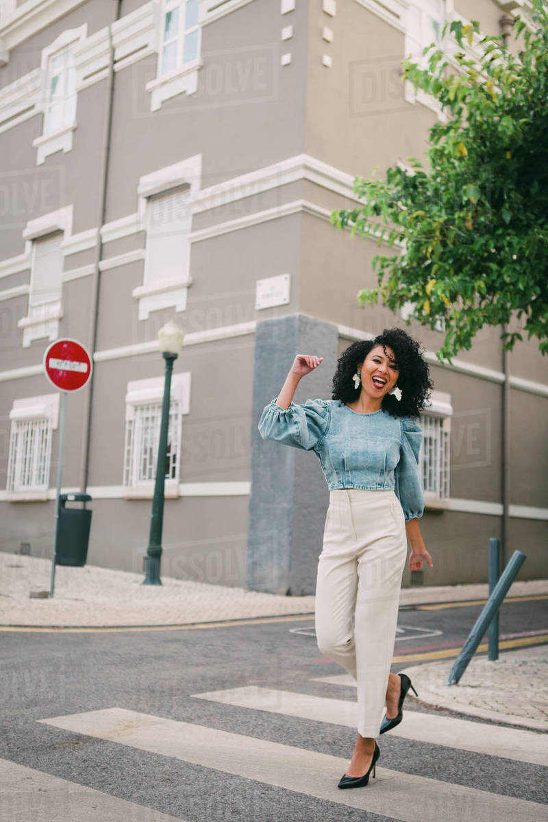 Portrait happy, carefree woman crossing city street Royalty-free stock photo