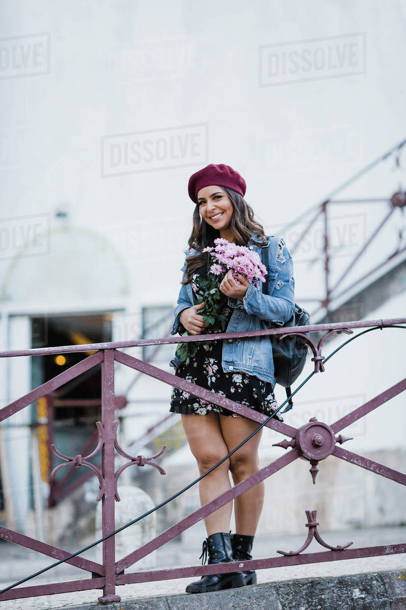 Portrait happy young woman in beret holding flower bouquet Royalty-free stock photo