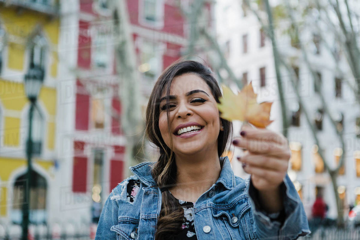 Portrait happy, playful young woman holding autumn leaf on urban street Royalty-free stock photo