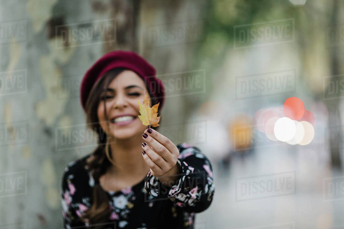 Portrait happy young woman holding autumn leaf Royalty-free stock photo