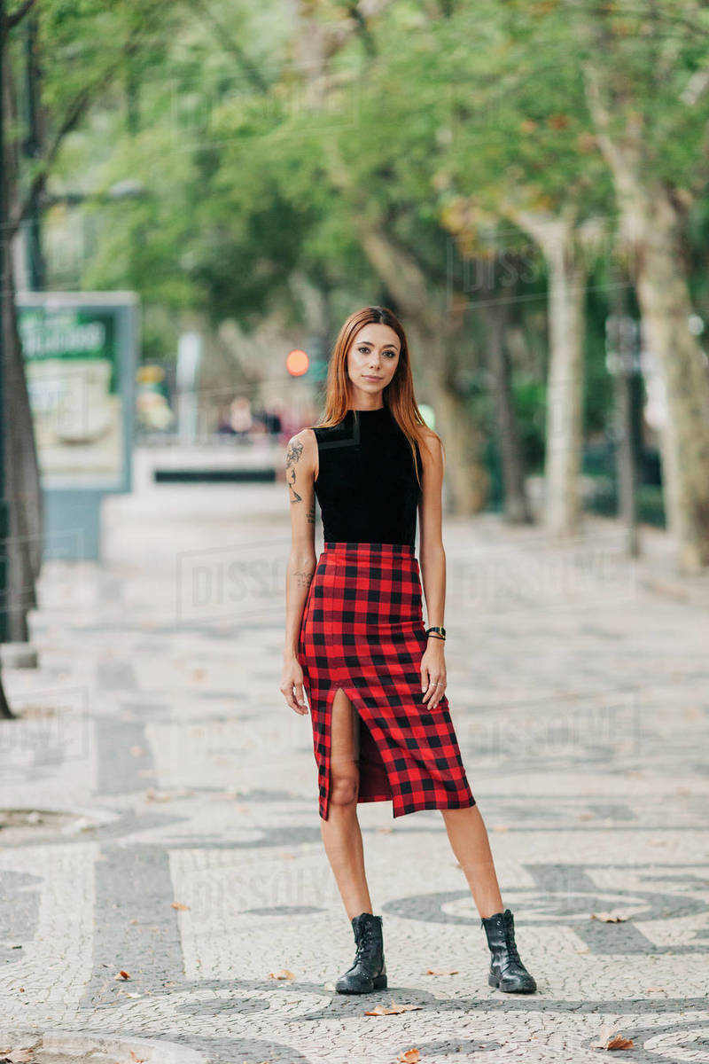 Portrait confident, stylish young woman wearing checked skirt in urban park Royalty-free stock photo