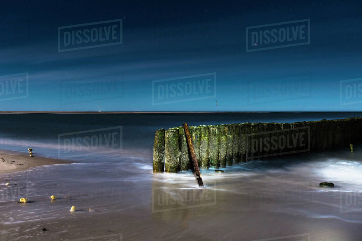 Ocean retaining wall illuminated at night Royalty-free stock photo