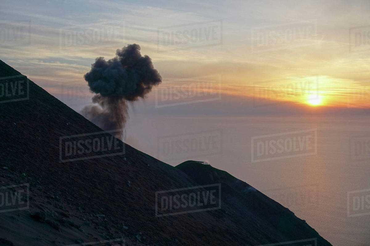 Ash plume rising along tranquil sunset ocean view, Mount Etna, Stromboli, Sicily, Italy Royalty-free stock photo
