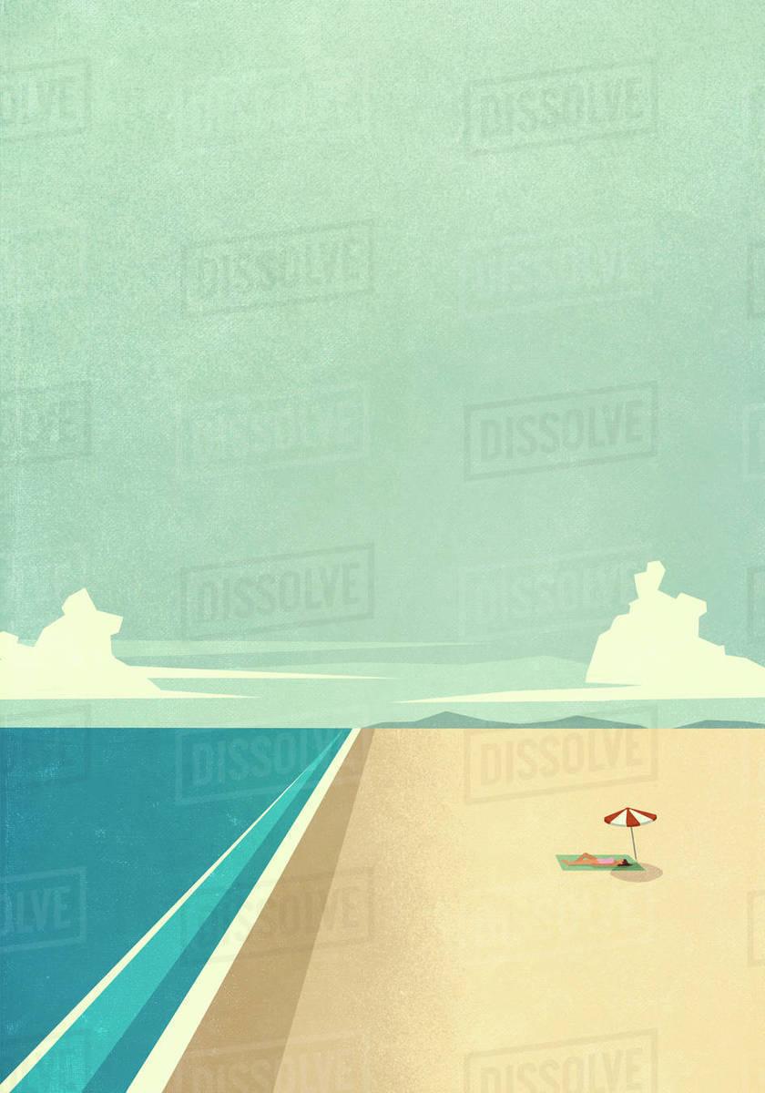 Woman sunbathing under umbrella on remote ocean beach Royalty-free stock photo
