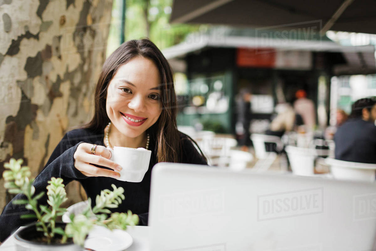 Portrait confident woman drinking coffee at laptop on sidewalk cafe Royalty-free stock photo