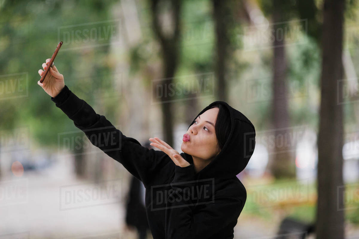 Confident, playful woman taking selfie with camera phone, blowing a kiss Royalty-free stock photo