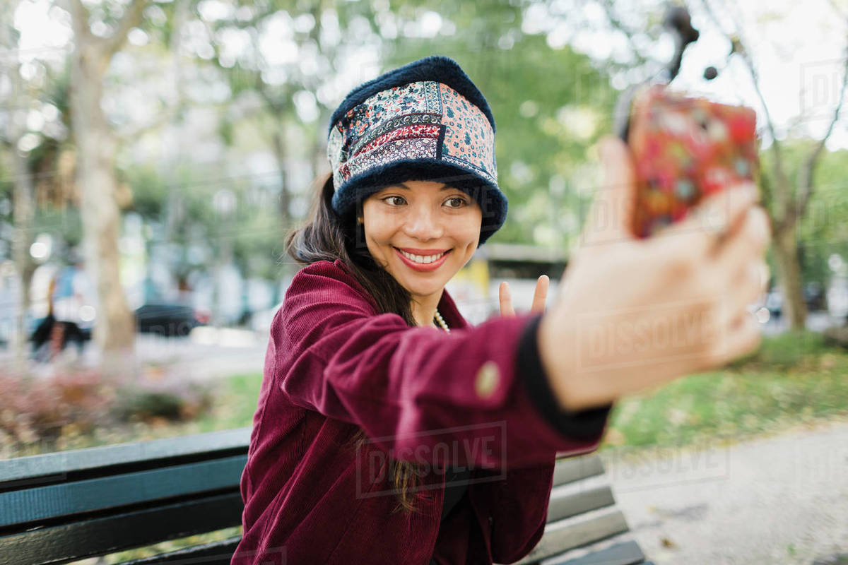 Happy woman taking selfie with camera phone on park bench Royalty-free stock photo