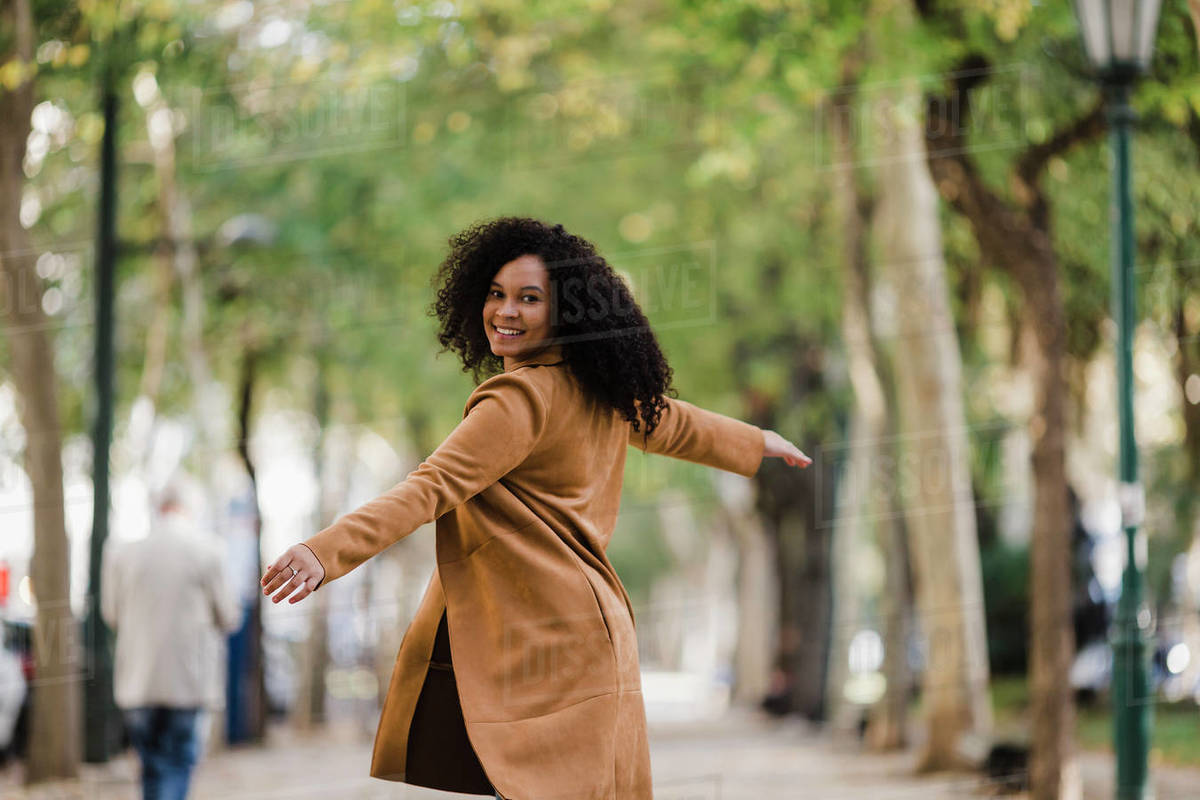 Portrait carefree young woman dancing on treelined sidewalk Royalty-free stock photo