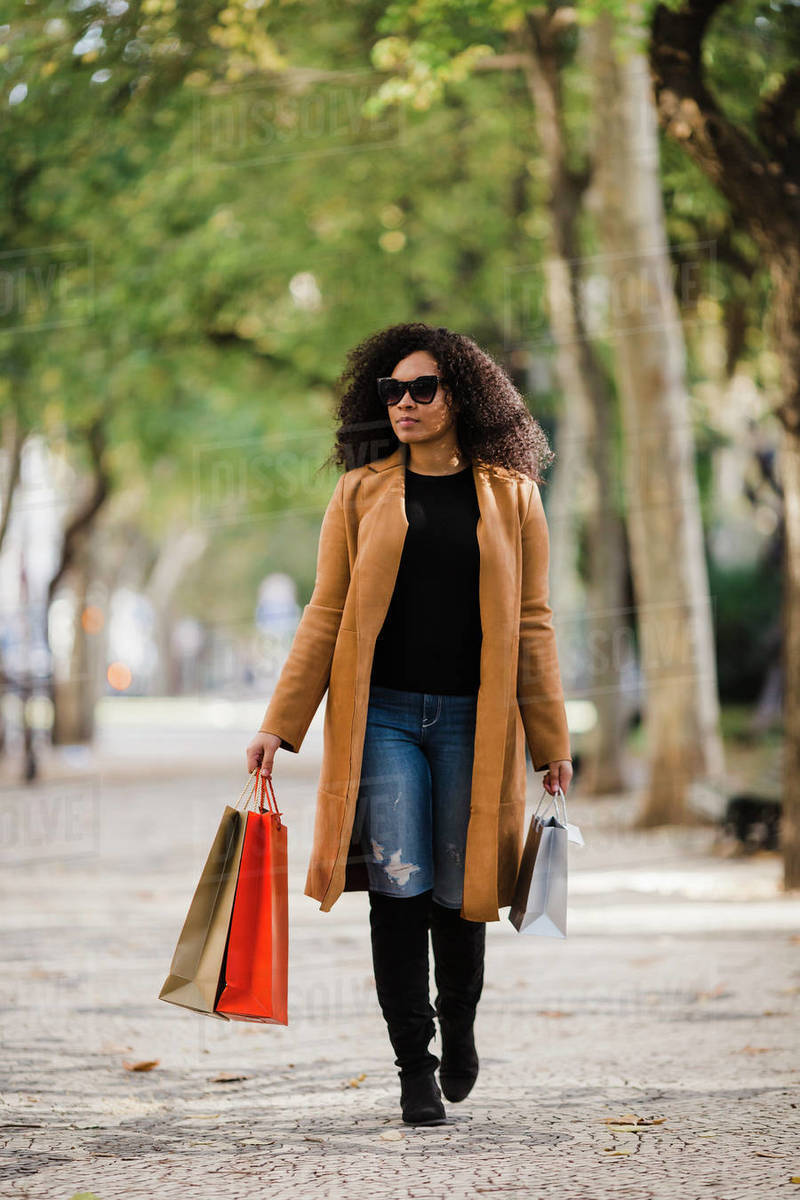 Stylish young woman walking with shopping bags on sidewalk Royalty-free stock photo