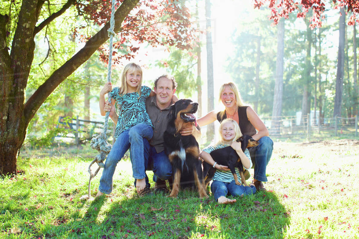 Portrait happy family with dogs in sunny autumn park Royalty-free stock photo