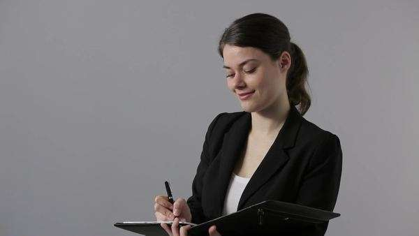 Businesswoman writing in a portfolio and smiling at camera, medium shot, Lockdown Royalty-free stock video