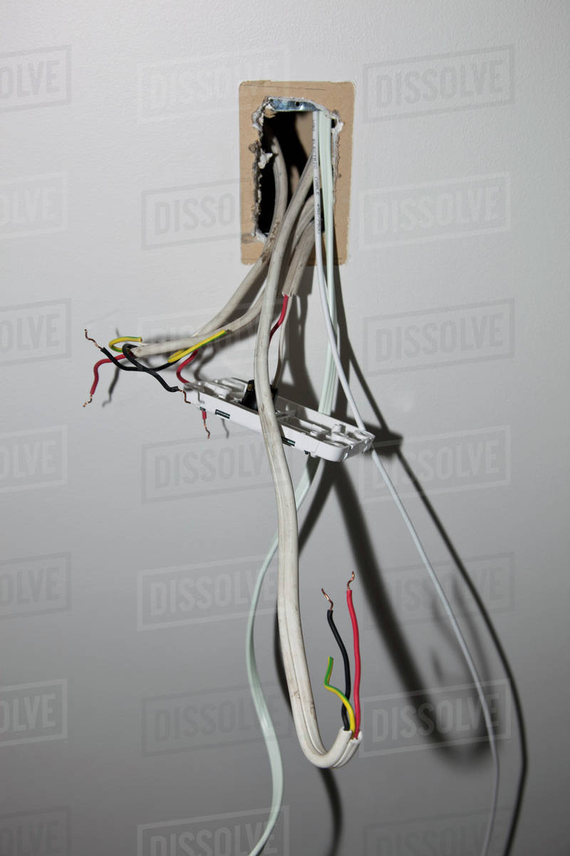 Wires and a switch coming out of a wall - Stock Photo - Dissolve