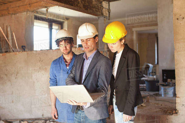 A building contractor and architects looking at a laptop at a building site Royalty-free stock photo