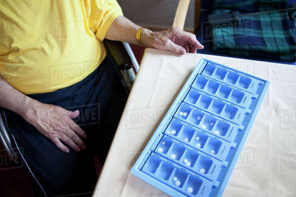 A senior man sitting next to a weekly pill organizer, focus on object Royalty-free stock photo