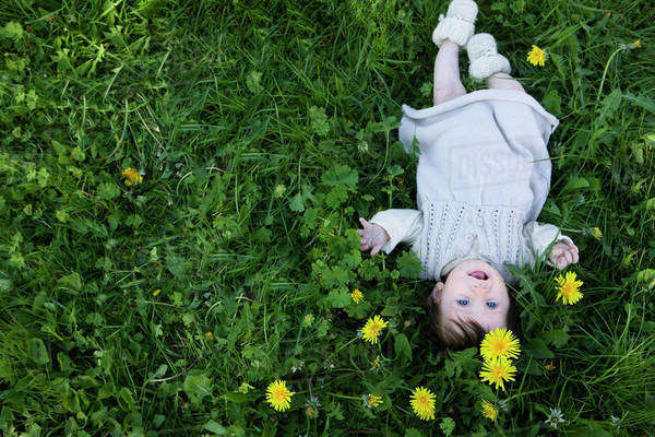 A cheerful baby girl lying in the grass, looking up Royalty-free stock photo