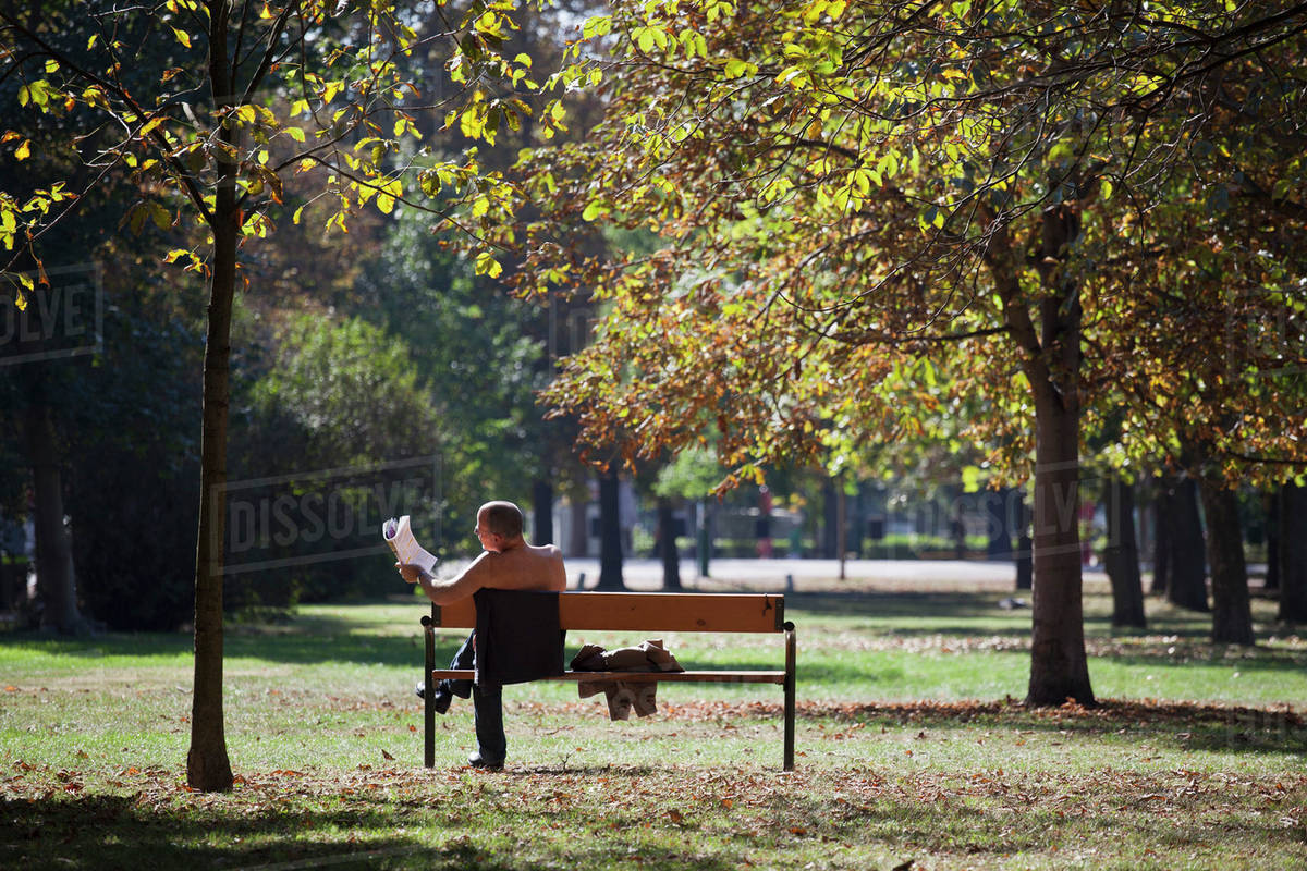 A Shirtless Businessman Reading A Newspaper On A Park Bench Stock